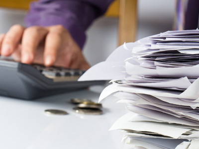 Person using calculator next to stack of papers with coins on table